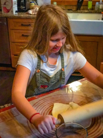 Nora in a battle of wills with the pizza dough.